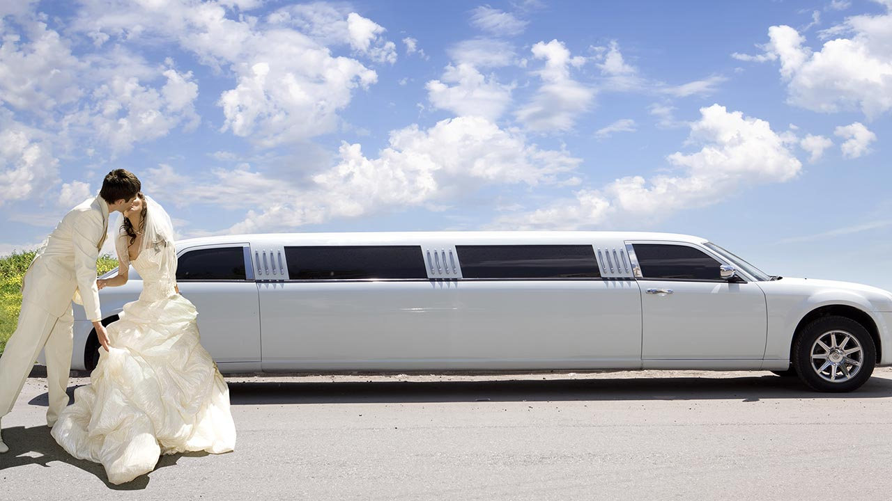 Couple celebrating a wedding, about to take a ride in a limousine.