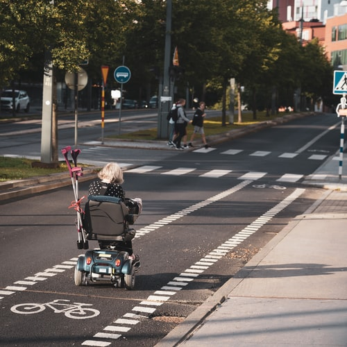 disabled woman in an electric wheelchair moving down the street
