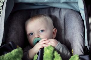 baby sitting in a baby car seat with a pacifier in his mouth